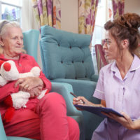 Care assistant checking menu choices with a resident