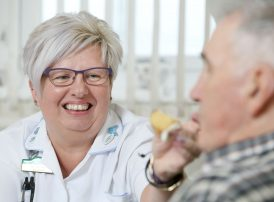 residents enjoying afternoon tea with smiling care assistant