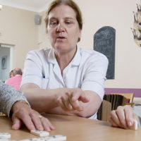 Residents playing scrabble with a care assistant