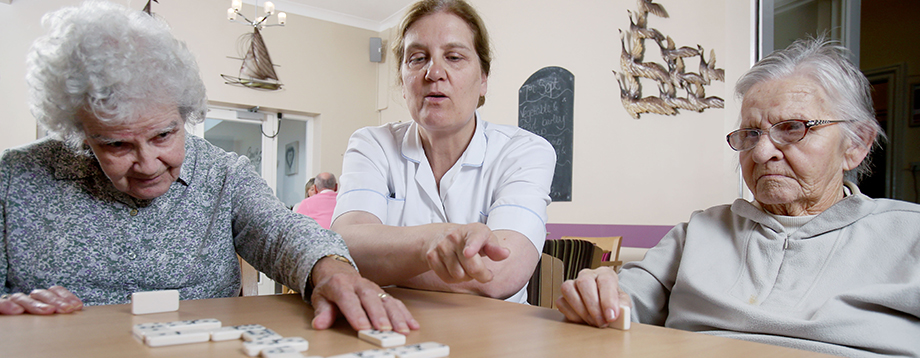 residents playing scrabble with care assistant