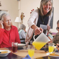 Residents enjoy a meal together helped by the Care Manager