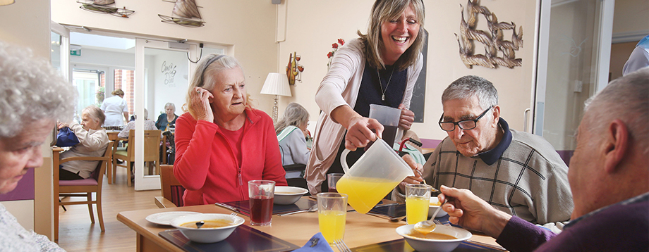 residents enjoy a meal together helped by care manager