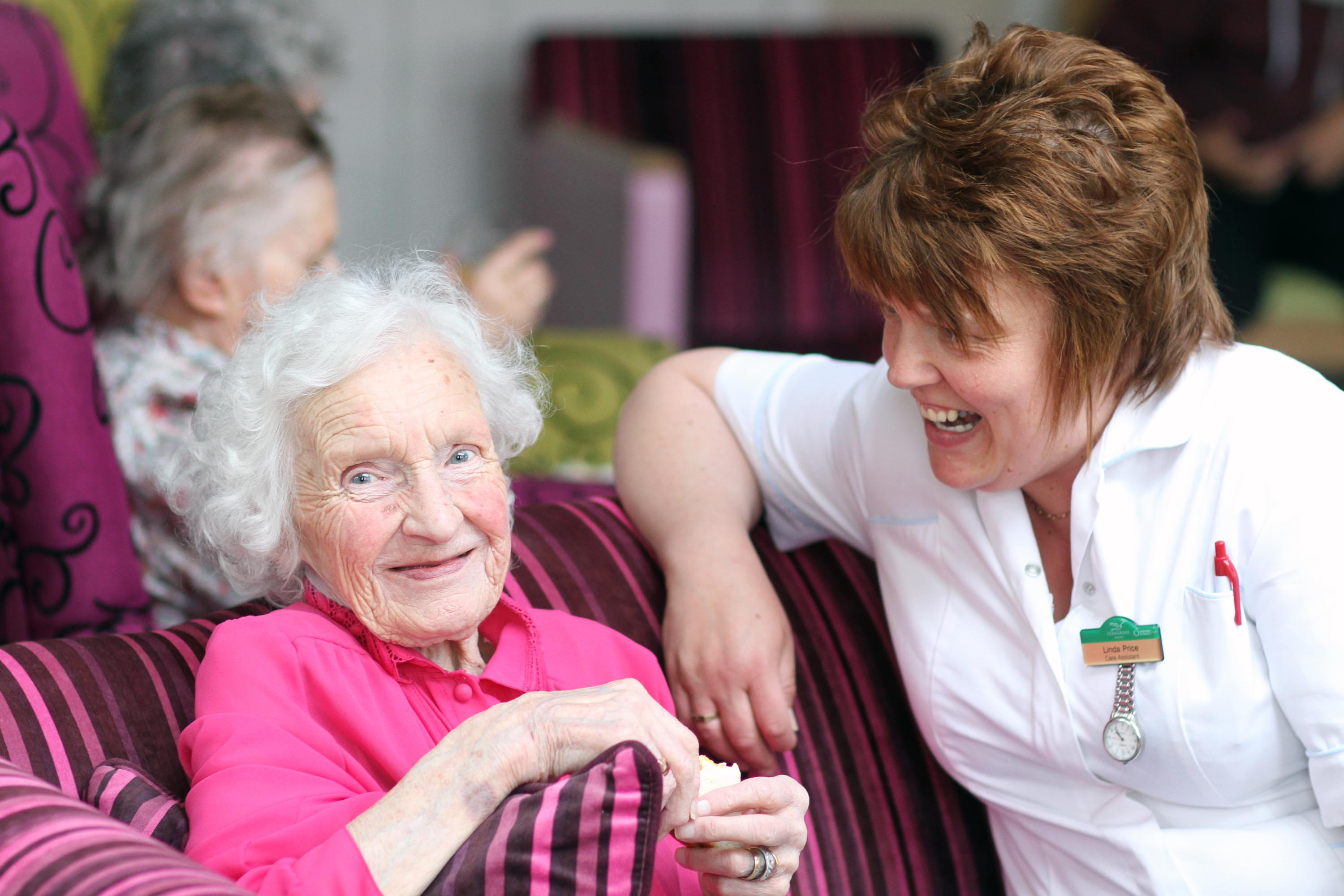 A happy resident with one of the care team