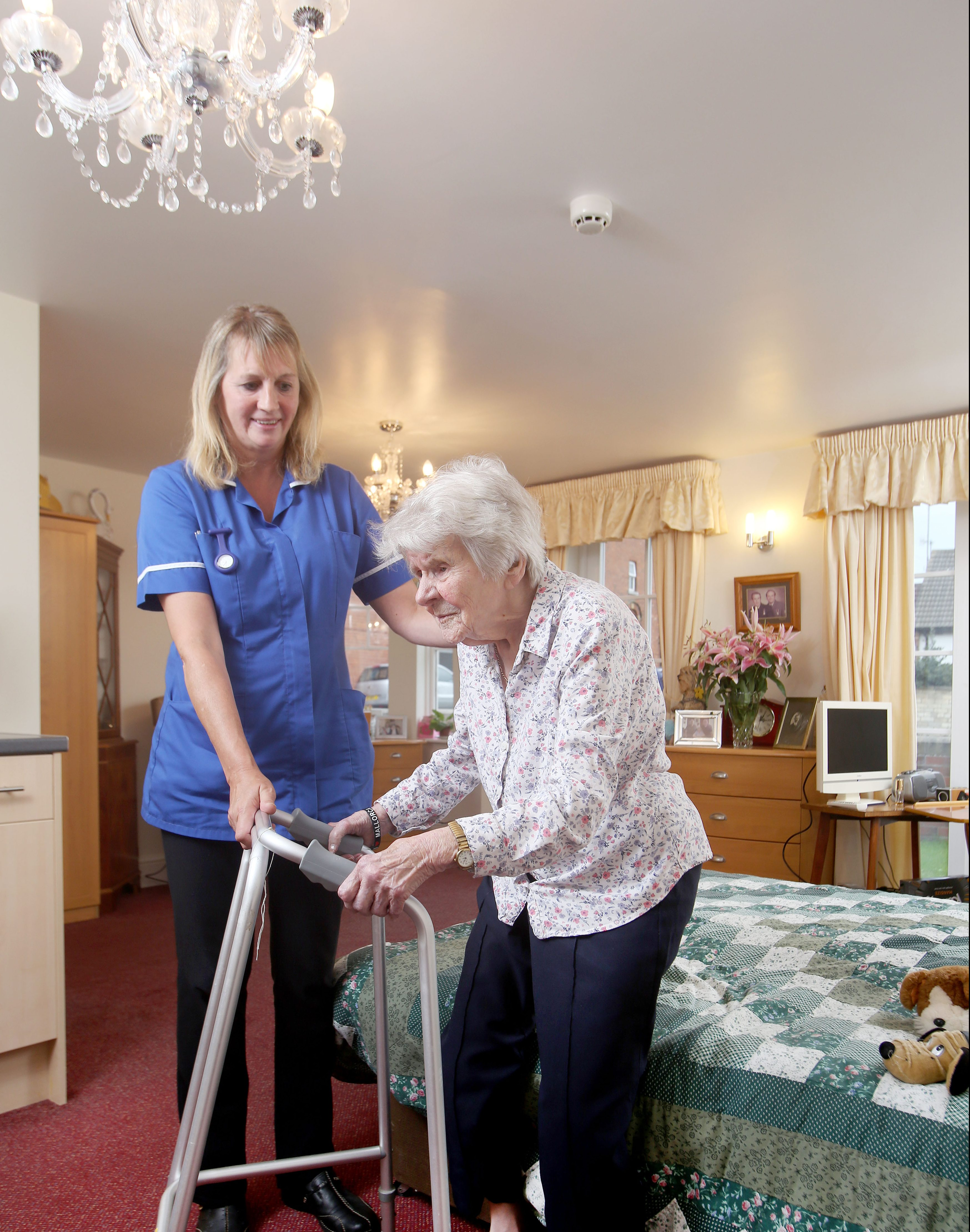 care assistant helping a resident in her room