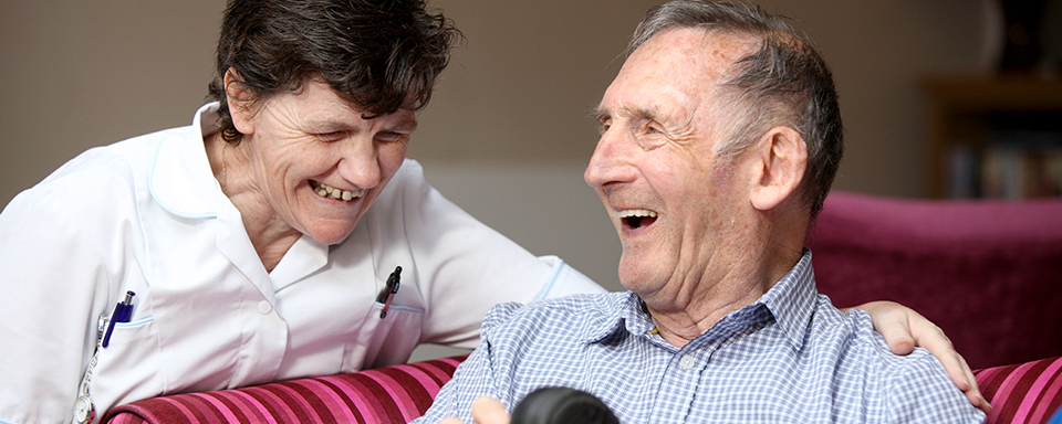 A resident and care assistant share a joke