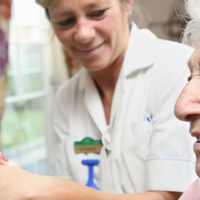 A resident enjoys watching a budgie with a care assistant